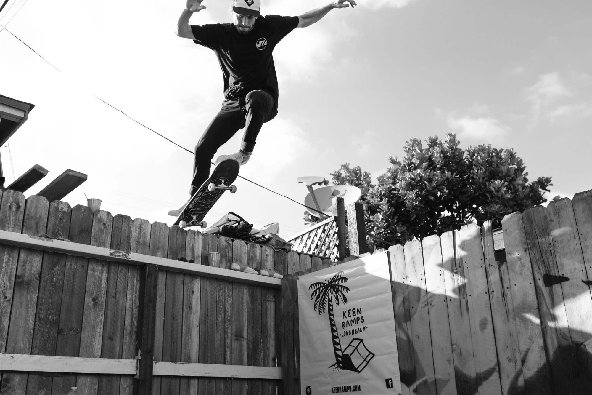 Cory dropping into a miniramp from the neighbors roof on his skateboard