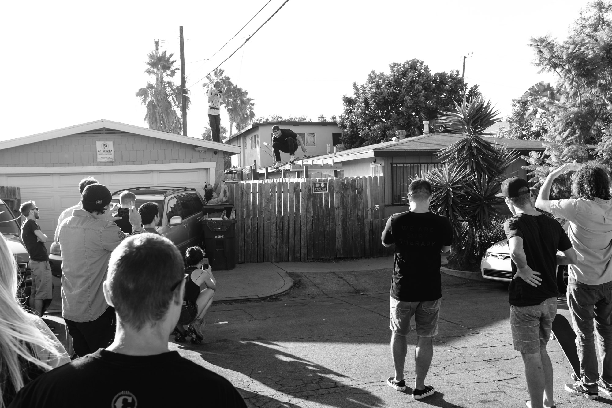 Cory ollies his back fence into the street while people watch.