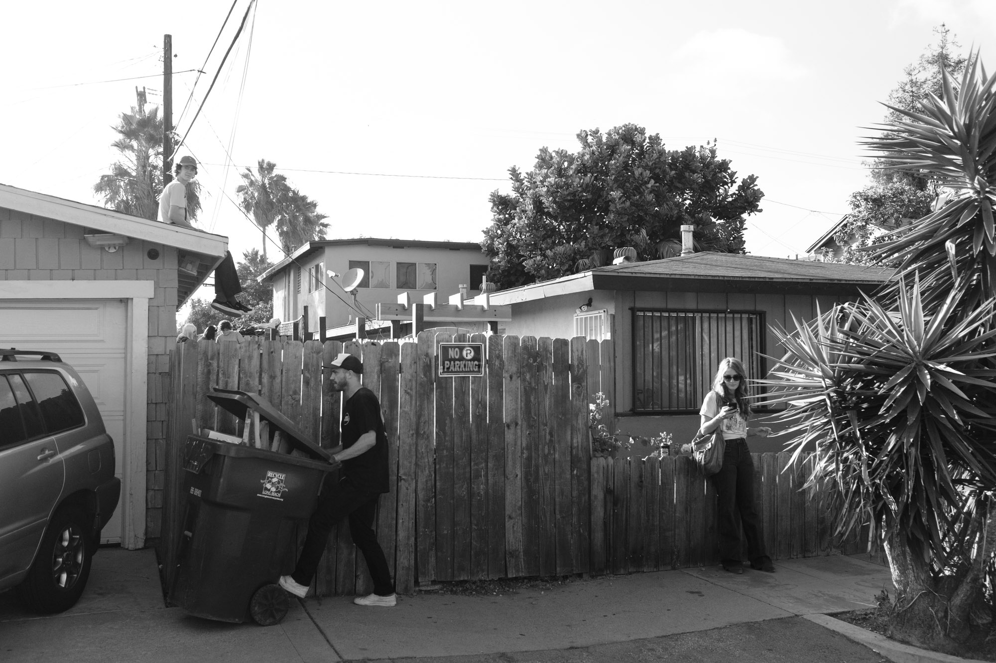 Cory moving a trash can near his fence