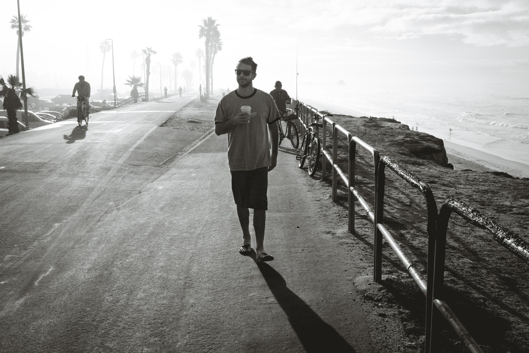 Ian waling the beach path with a coffee