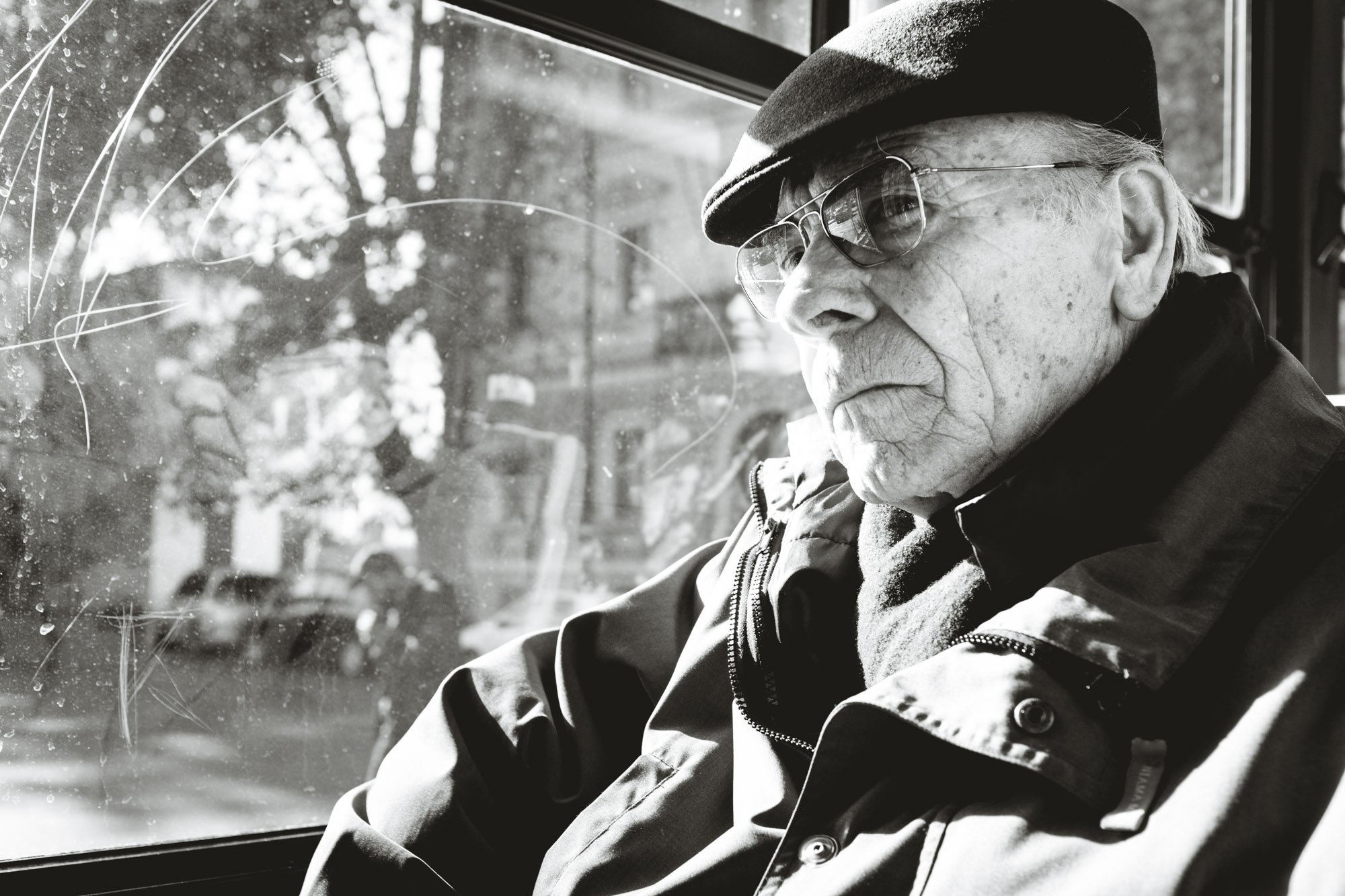 Old Man Looking Out Window of Bus