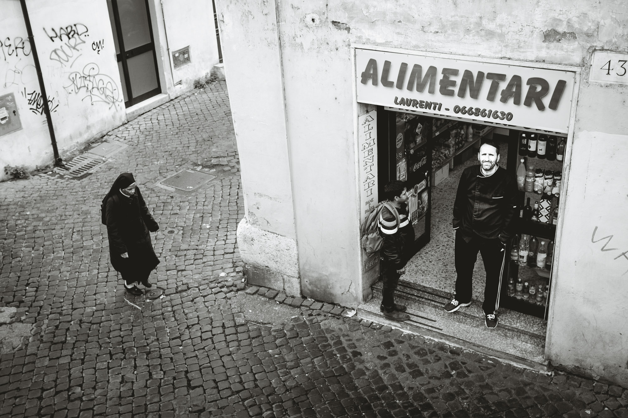 A nun walks by a storefront while two men talk. The street is made of stone pavers.