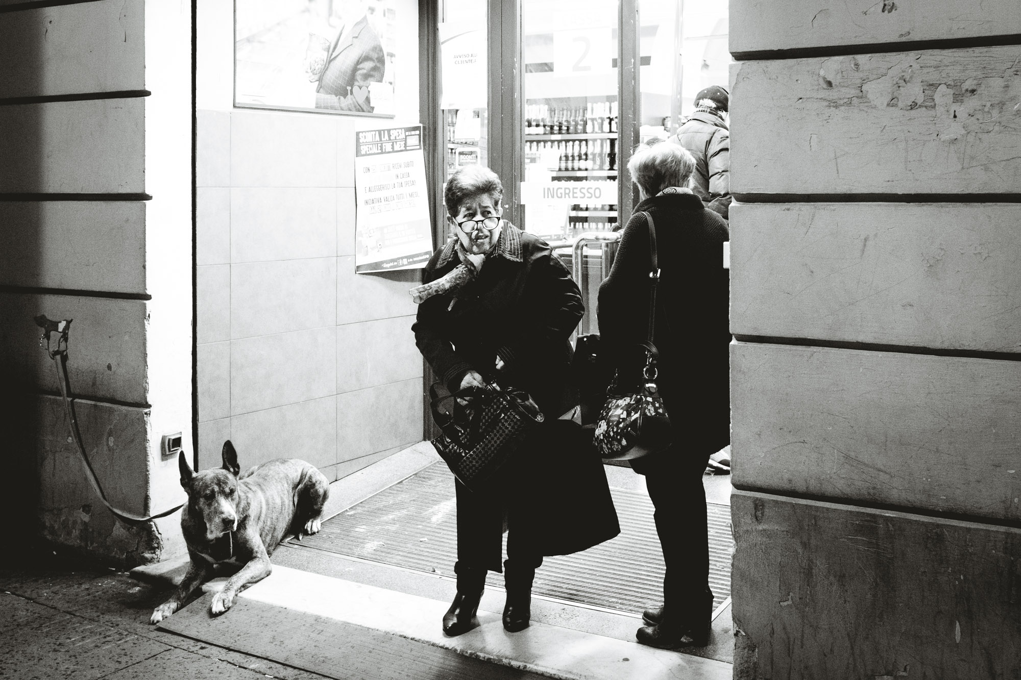 Woman waiting for bus in Rome near a dog