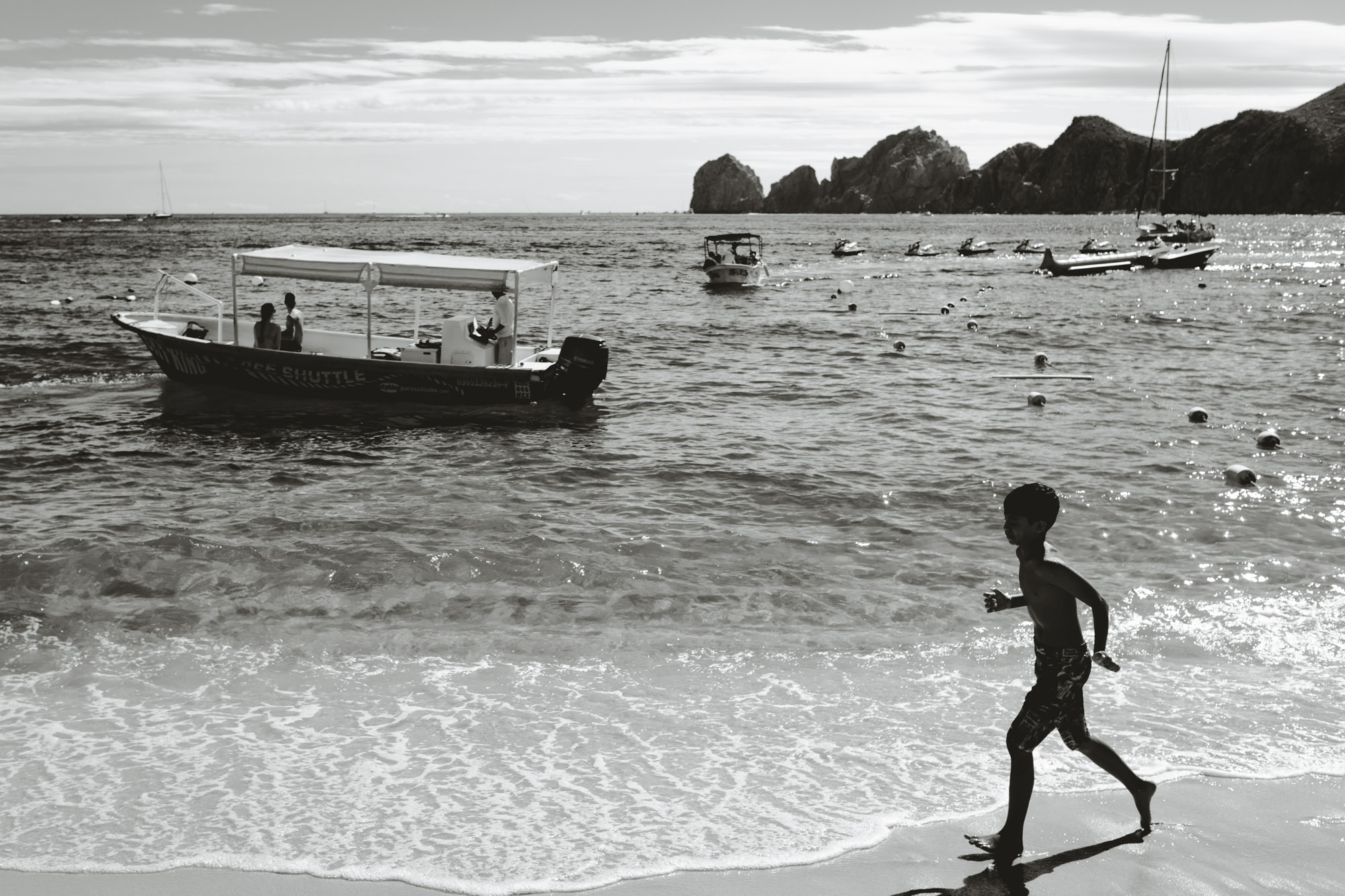 A boy's silhouette runs across the beach in Cabo San Lucas