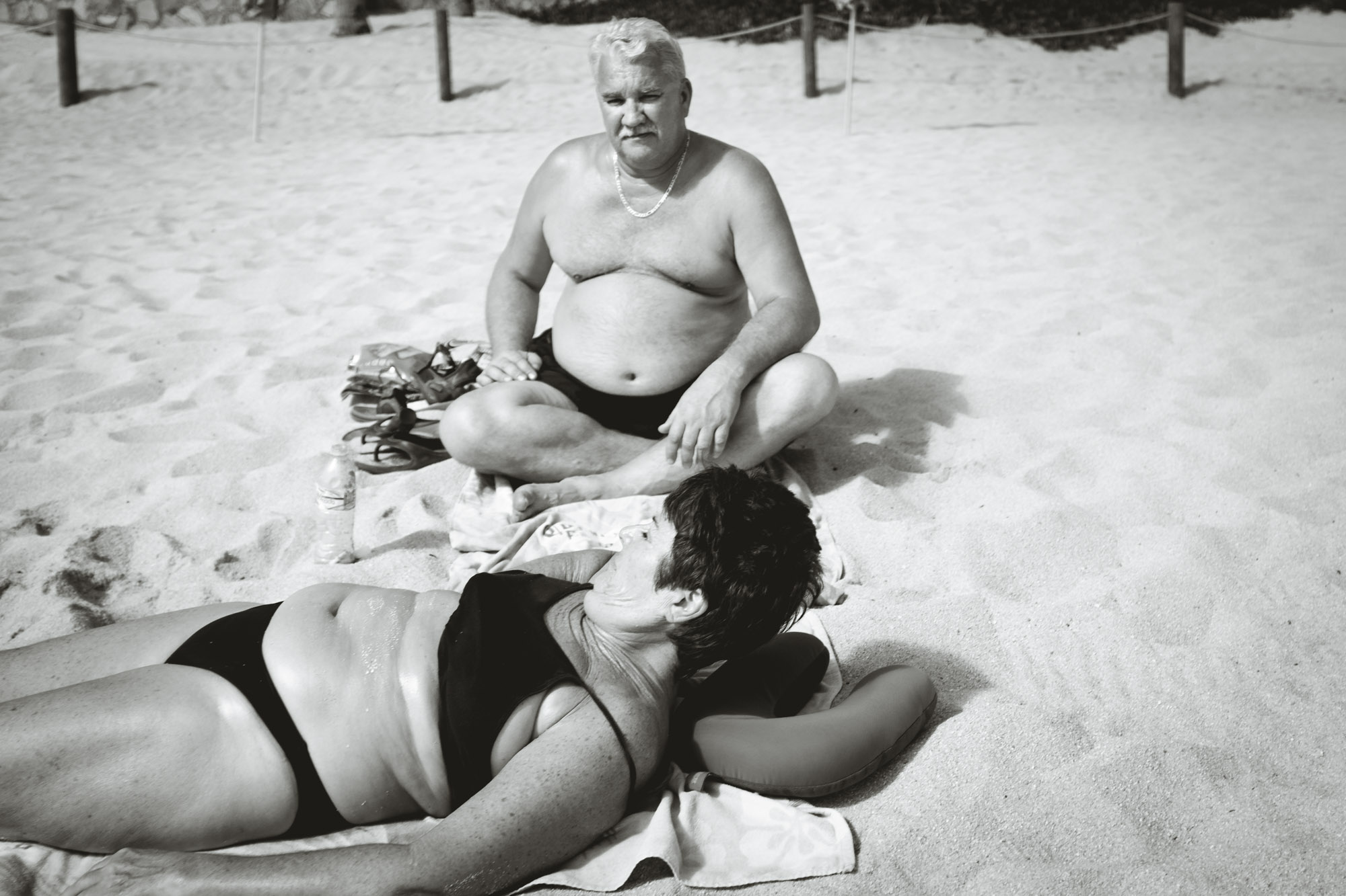 An older couple lounging on the beach in Cabo San Lucas