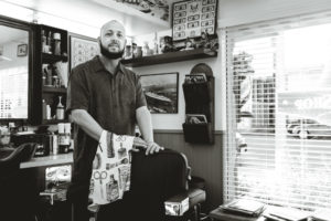 Jesse standing behind his chair at A Barber in Long Beach, CA.