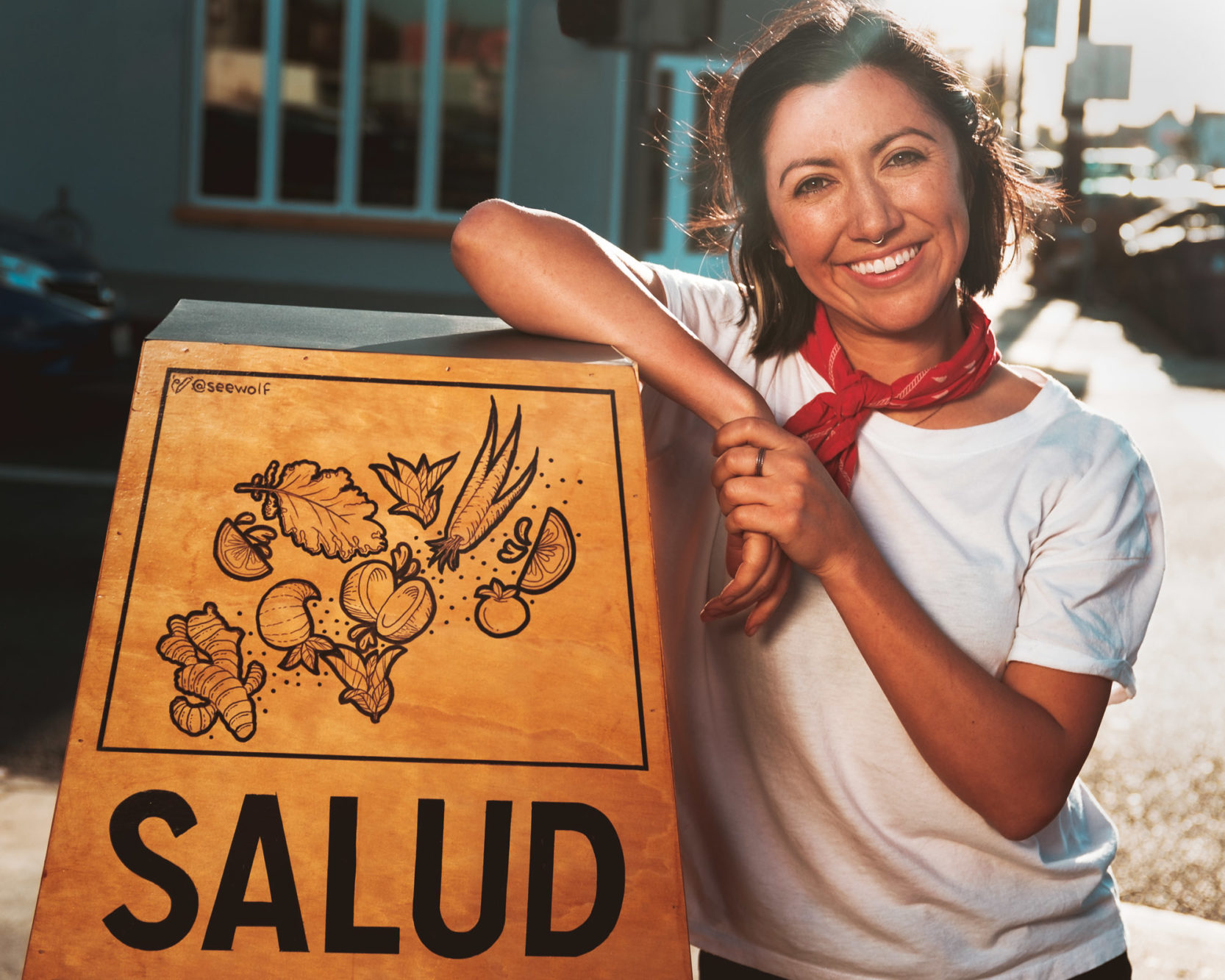 Angela-Almaguer-Salud-Standing-With-Sign