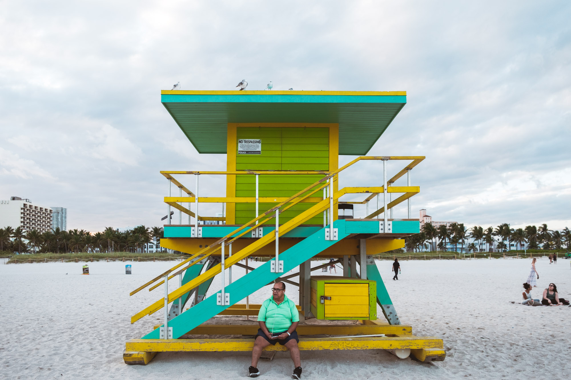 man-sitting-alone-south-beach-miami-florida