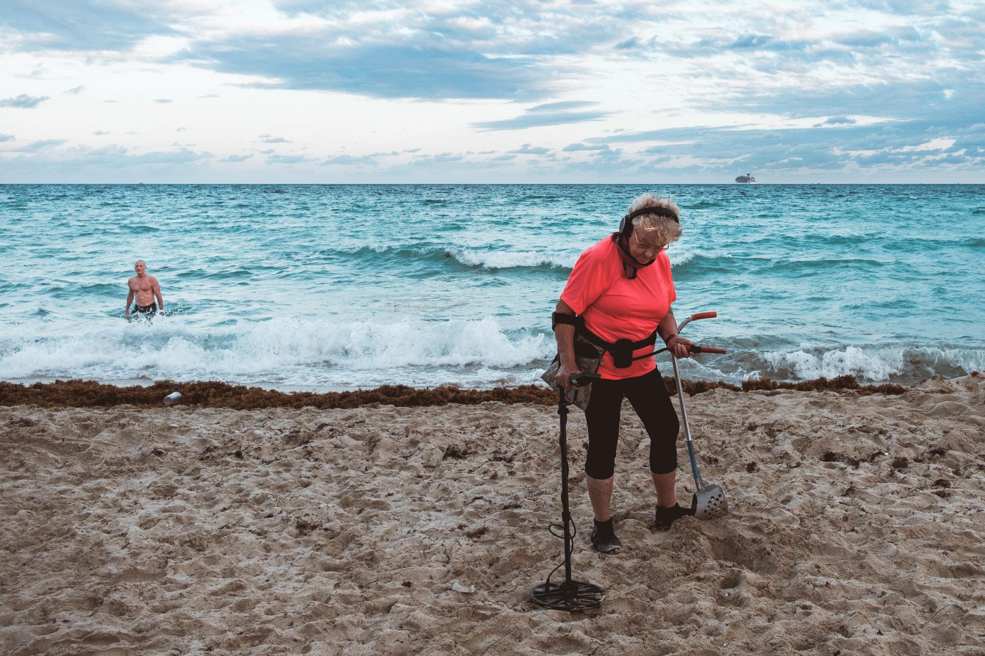 woman-searching-metal-detector-south-beach-miami-florida