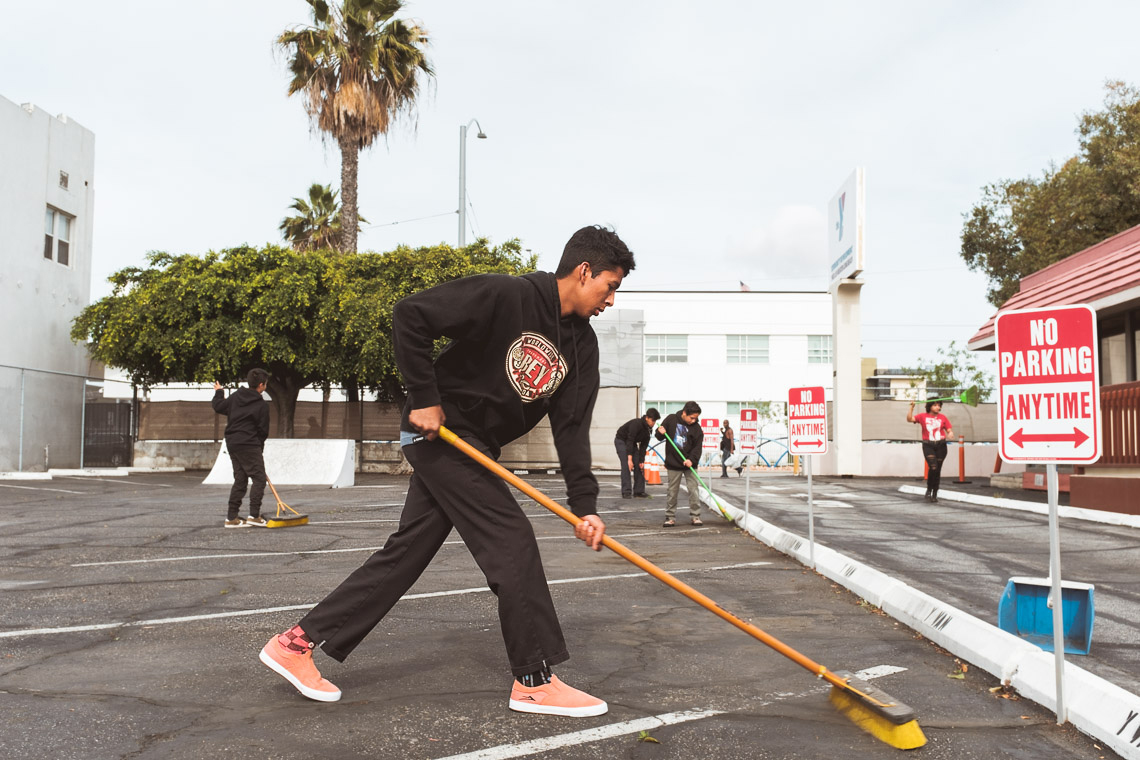 YMCA youth sweeping the parking lot at the Community Development YMCA in Long Beach California.