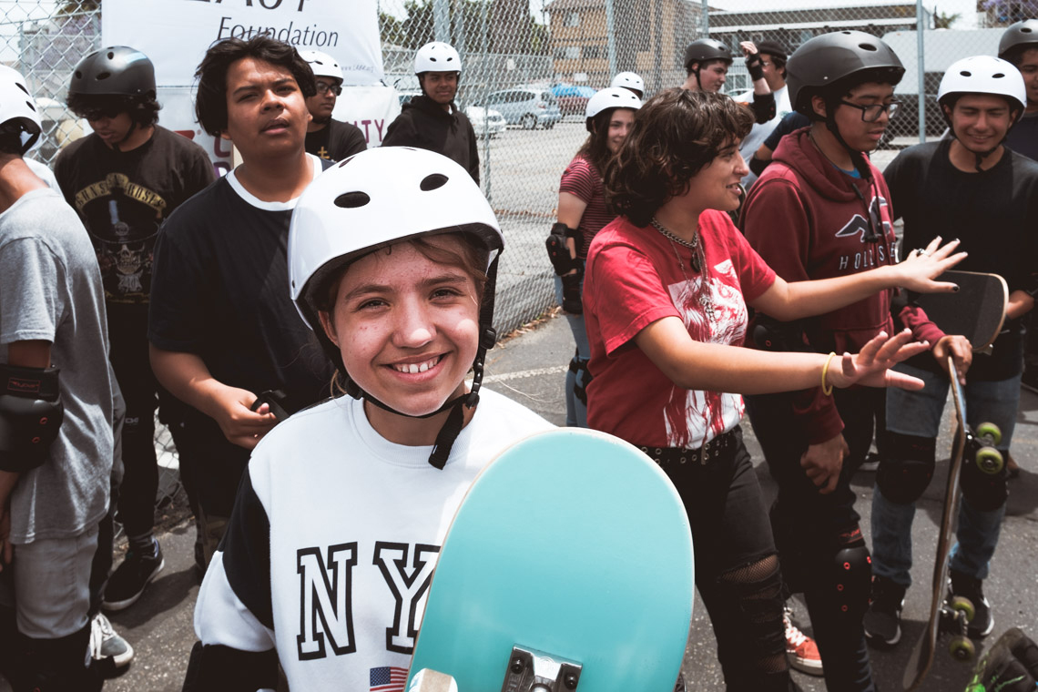 Girl with helmet smiling at the camera during the Skate Fest at the Community Development YMCA.