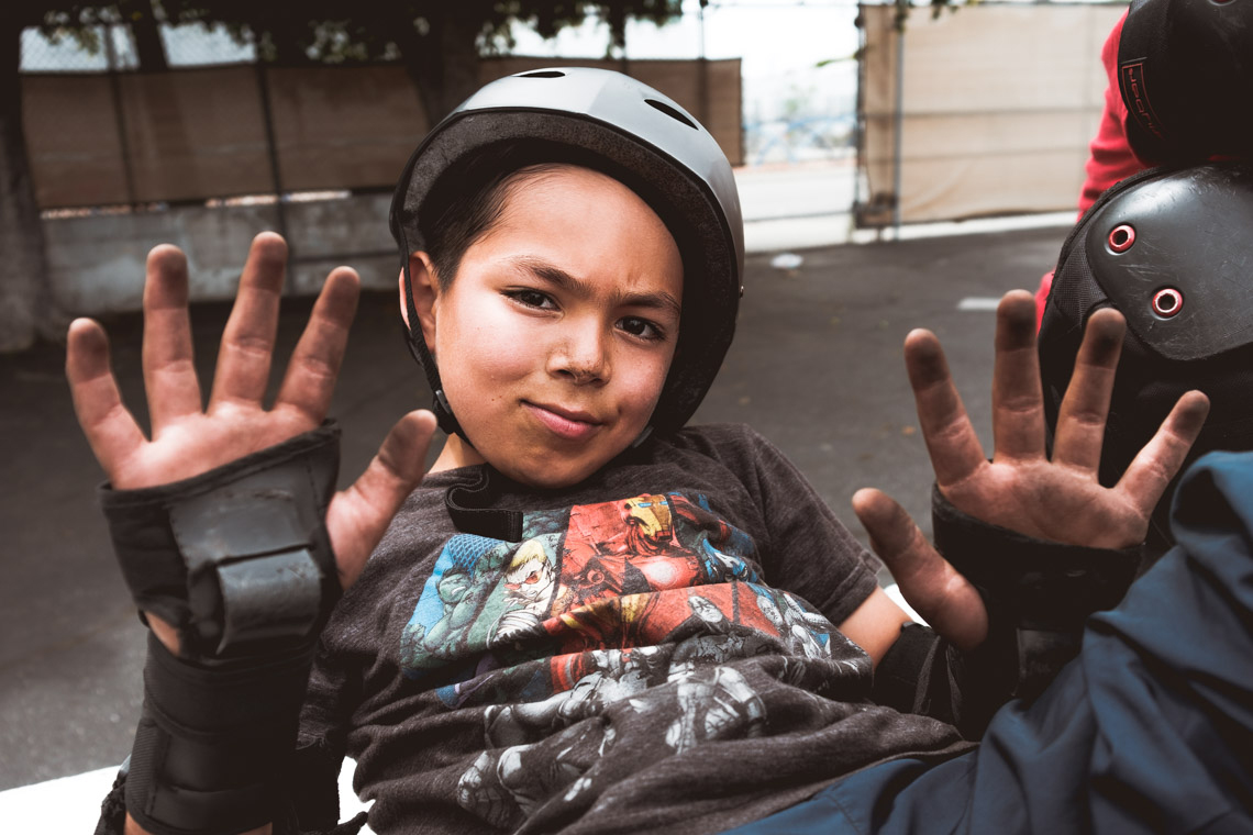 Elementary aged boy in helmet shows his dirty hands during the Skate Fest at the Community Development YMCA.