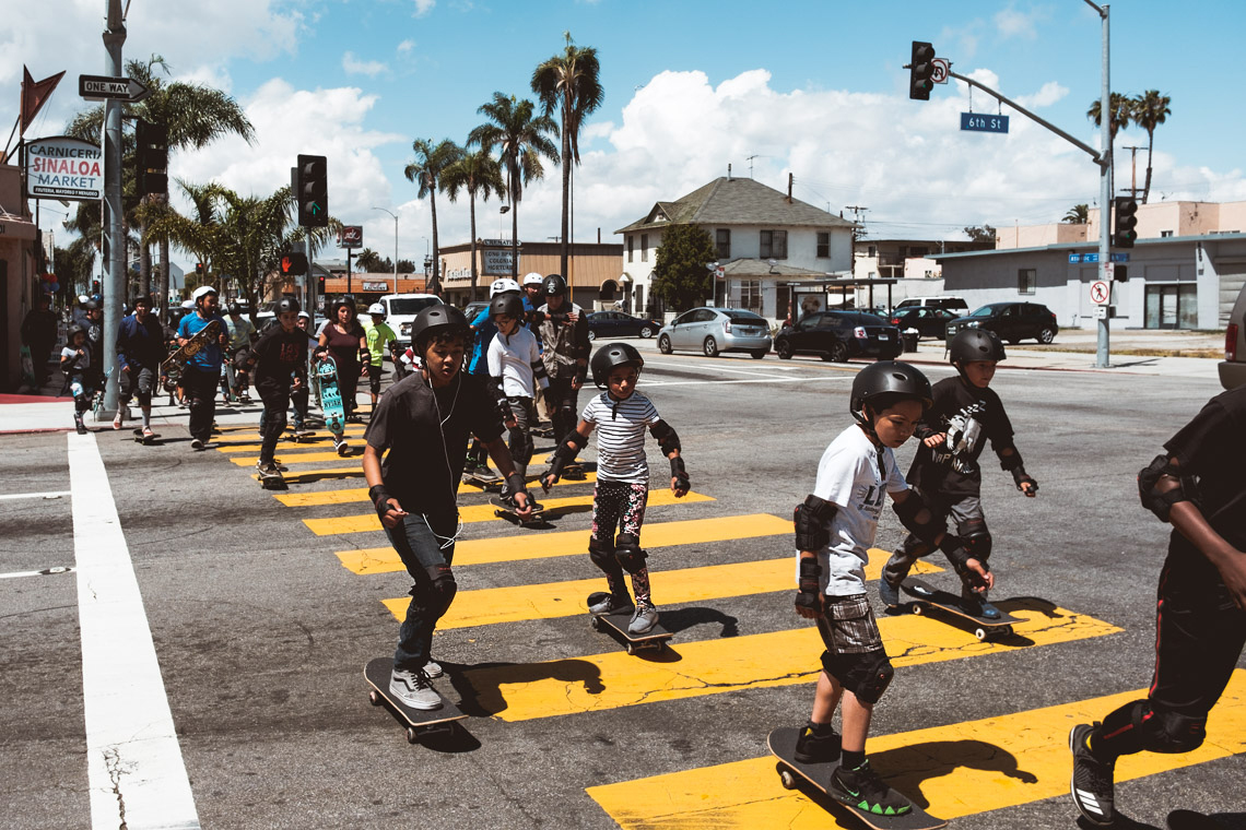 Group of kids skateboarding on the crosswalk in downtown Long Beach during the Skate Fest at the Community Development YMCA.