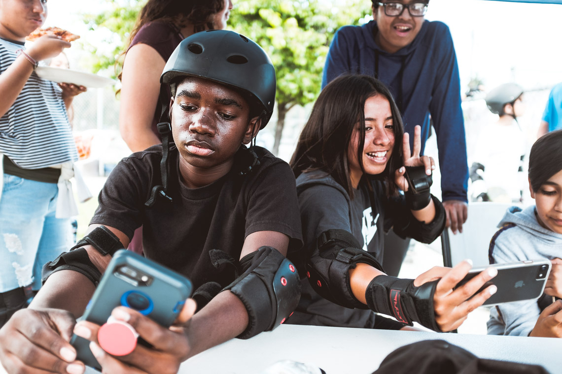 Teens taking a phone break and selfie during the Skate Fest at the Community Development YMCA.