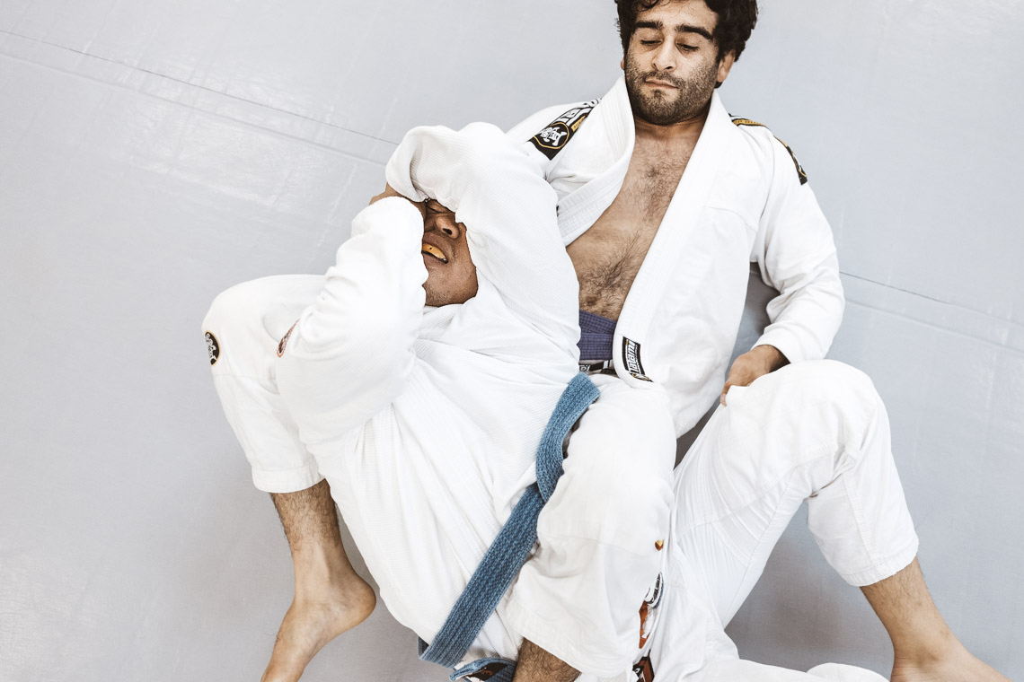 jiu jitsu practitioner hitting a bow and arrow choke on a teammate