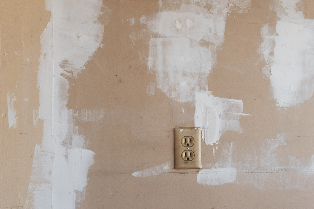 Patched up wall in garage with outlet